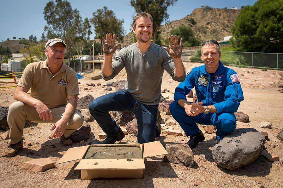 """Actor Matt Damon, who stars as NASA Astronaut Mark Watney in the film """"The Martian,"""" smiles after having made his hand prints in cement at the Jet Propulsion Laboratory (JPL) Mars Yard, while Mars Science Lab Project Manager Jim Erickson, left, and NASA Astronaut Drew Feustel look on, Tuesday, Aug. 18, 2015, at the JPL in Pasadena, California. While at JPL Damon meet with NASA scientists and engineers who served as technical consultants on the film. The movie portrays a realistic view of the climate and topography of Mars, based on NASA data, and some of the challenges NASA faces as we prepare for human exploration of the Red Planet in the 2030s. Photo Credit: NASA/Bill Ingalls"""