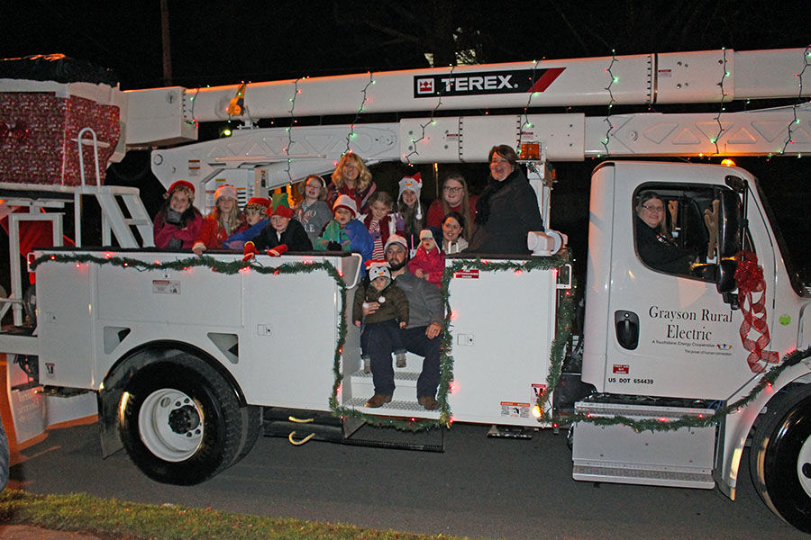 Employees of Grayson RECC pile onto the bucket truck they decorated to participate in the community parade. Photo: Marsha Thacker